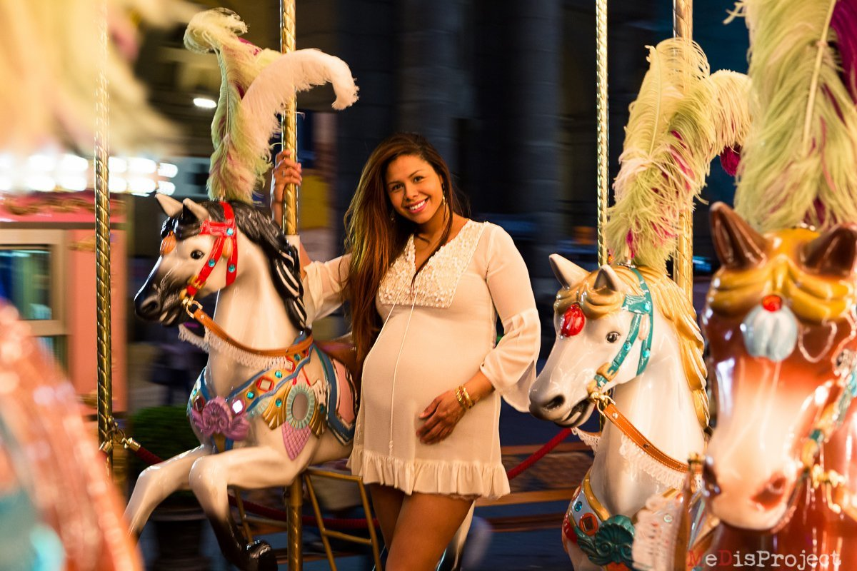 pregnant woman taking a ride on a Carousel