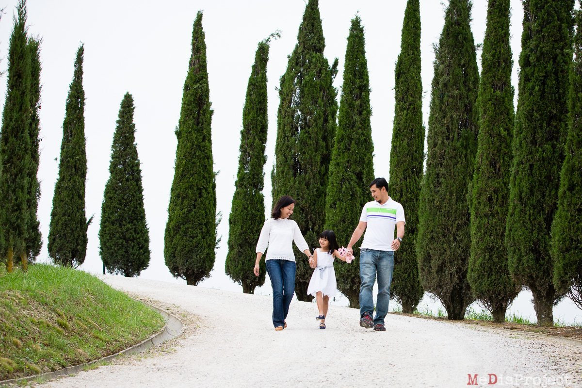 asian family walking down a cypress alley
