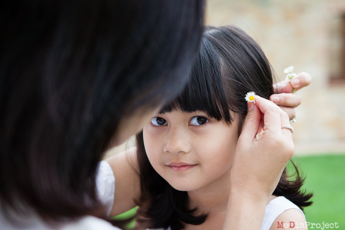mother putting daisies through her daughter's hair