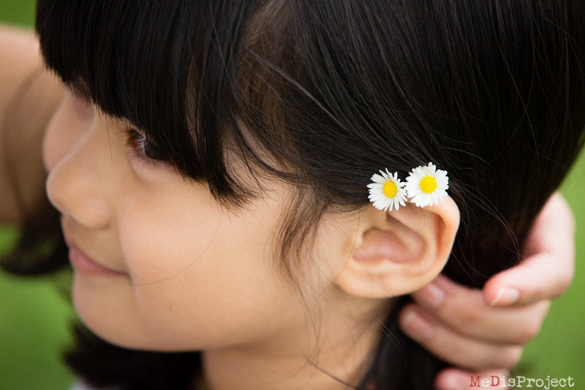 daisies through the hair of a little girl