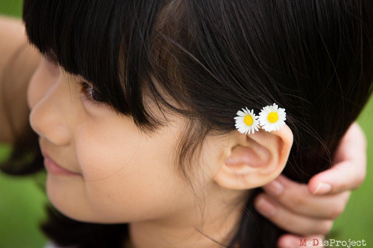 daisies through the hair of a little girl