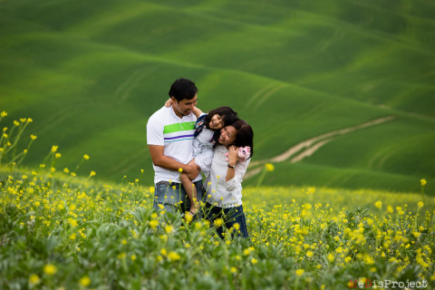 outdoor malay family portrait in the green fields of val d'orcia