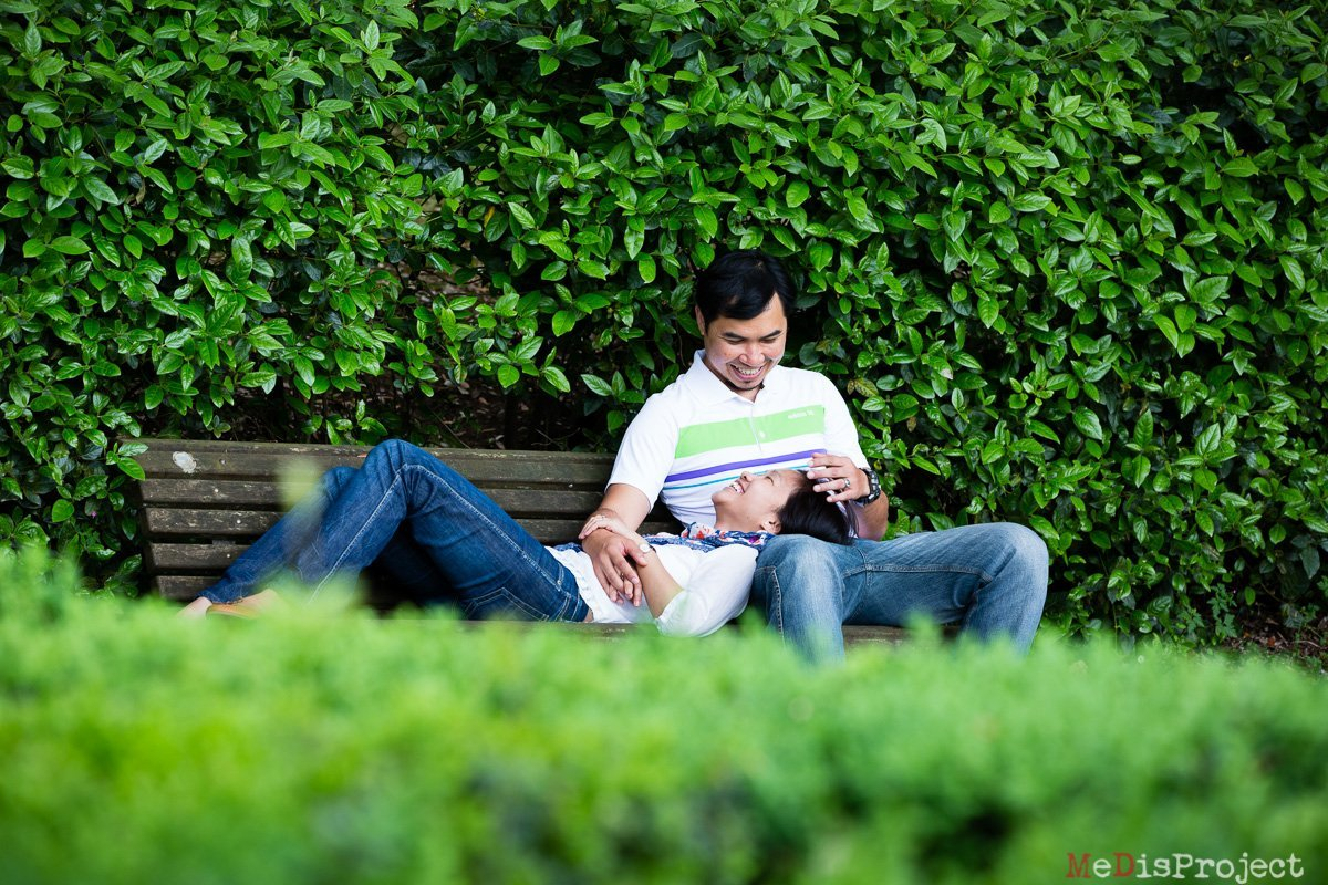couple relaxing on a bench between green hedges