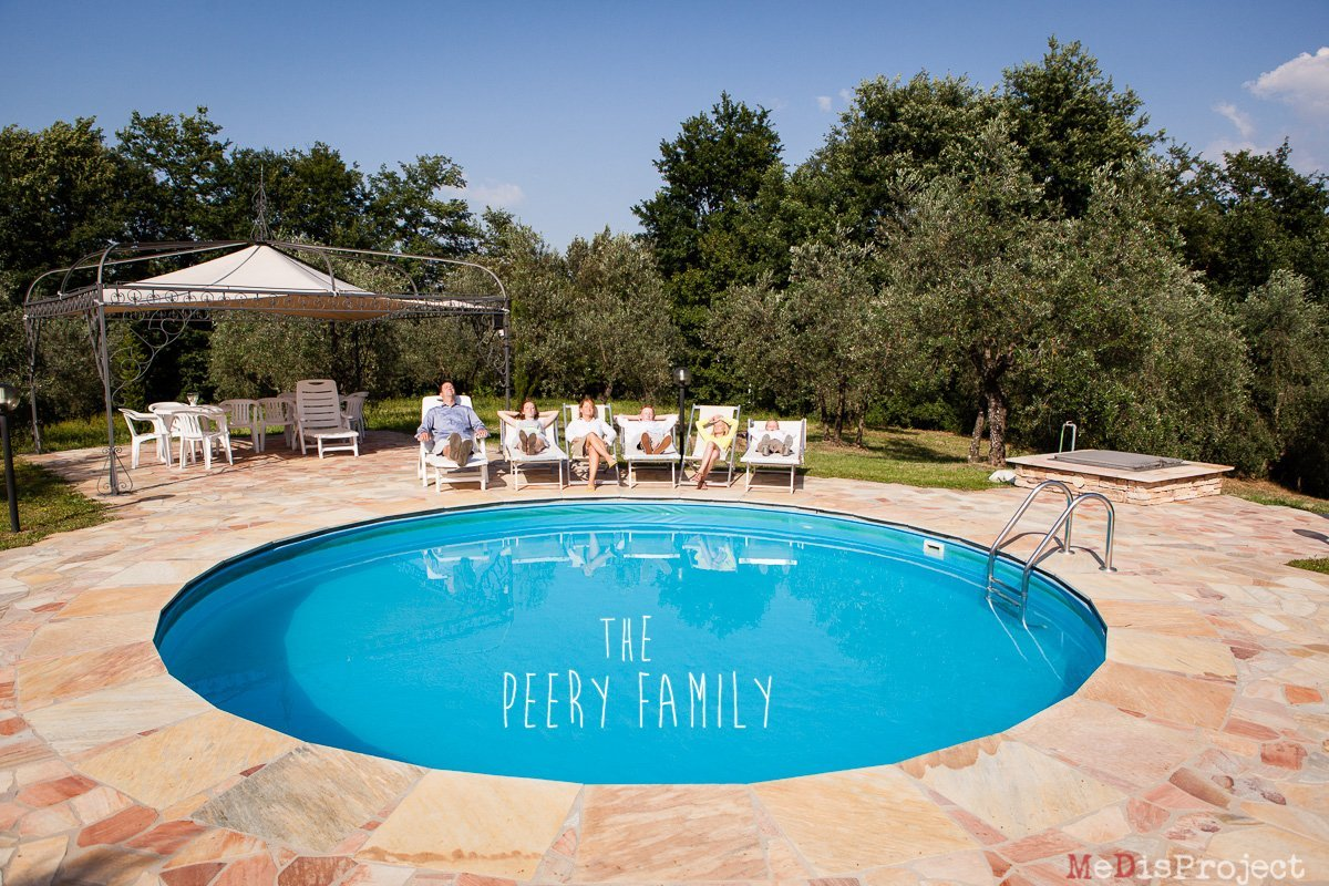 family of five sunbathing by the pool during a holiday in tuscany
