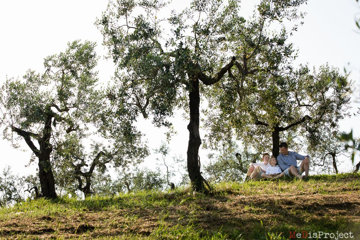 father and sons sitting under an olive tree in tuscany