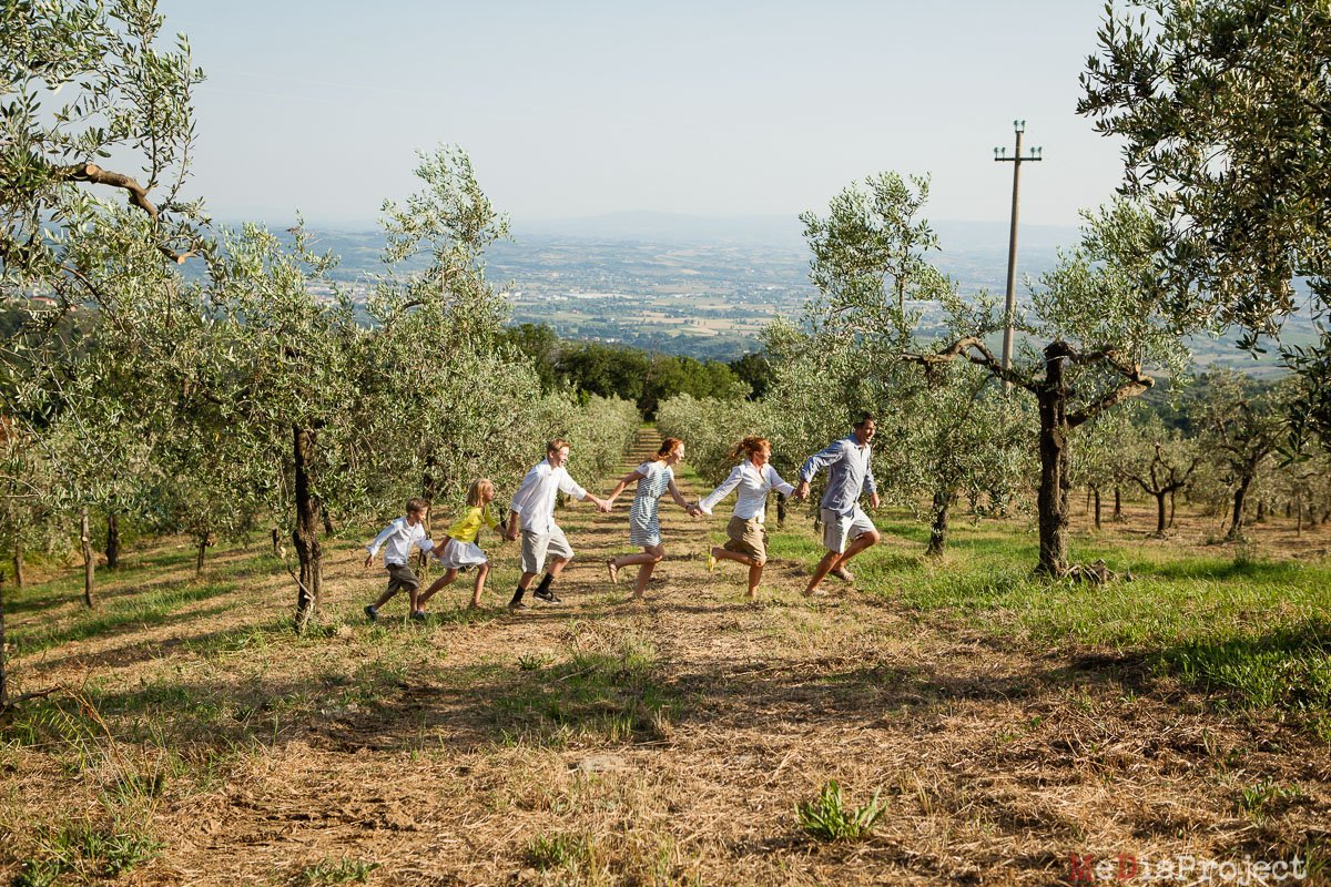 big family of five running hand by hand in tuscany
