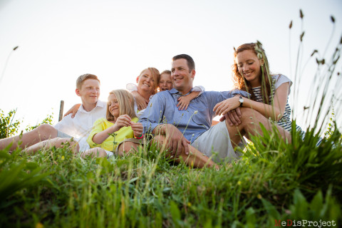 big family portrait sitting on the grass in tuscany