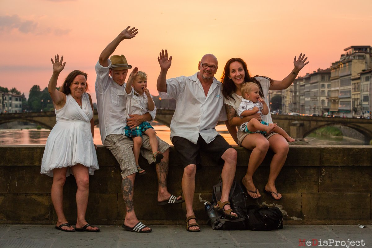 family of six waving at sunset on a bridge of florence