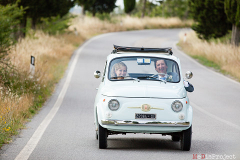 bride and groom riding a fiat 500 in tuscany