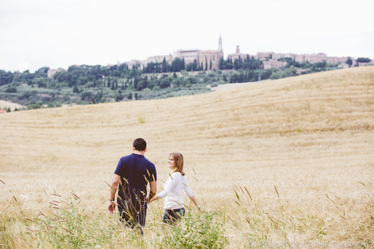 romantic couple in the fields of wheat with Pienza on the background