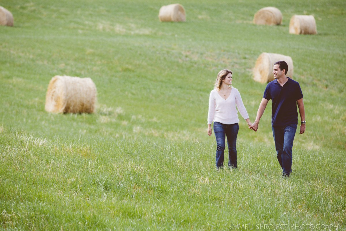 a romantic couple and the field of hay bales