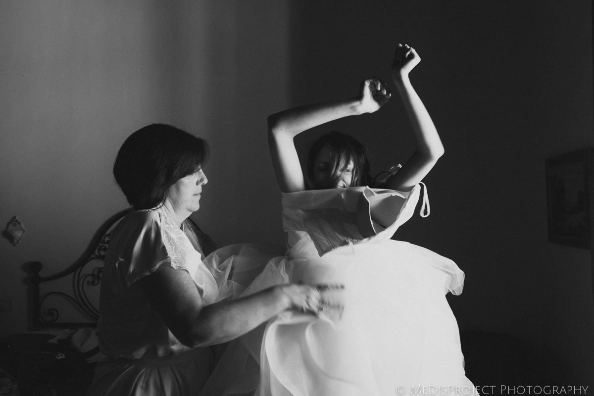 mother helping a bride to put her dress on