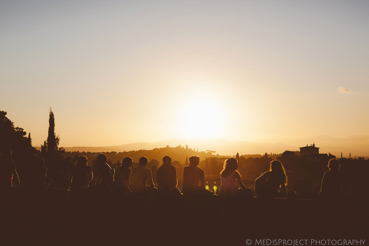 people sitting watching sunset from San Miniato church in Florence