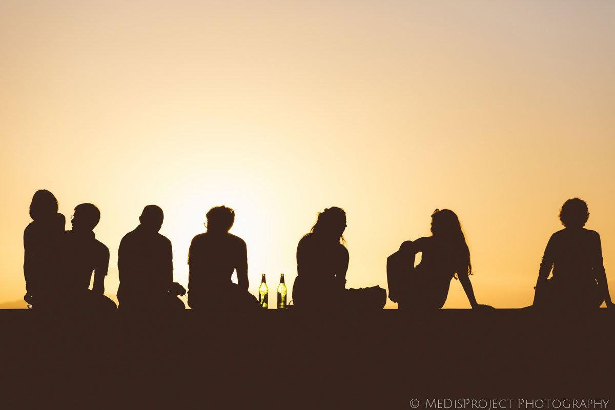 People sitting drinking beer and enjoying sunset in Florence