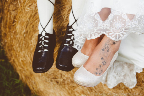 bride and groom's feet with typical scottish shoes and tattoed feet