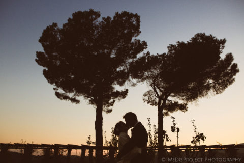 bride and groom's silhouette kissing at dusk