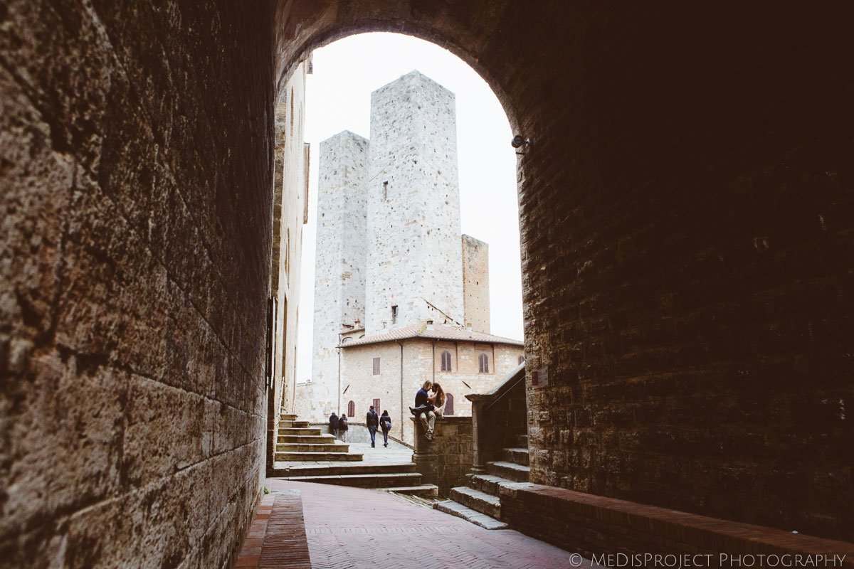 couple sitting in san gimignano surrounded by medieval towers