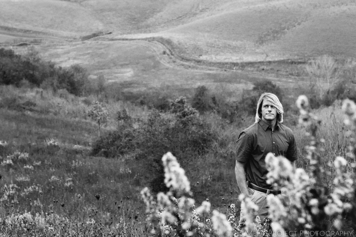 handsome blond man standing in a field