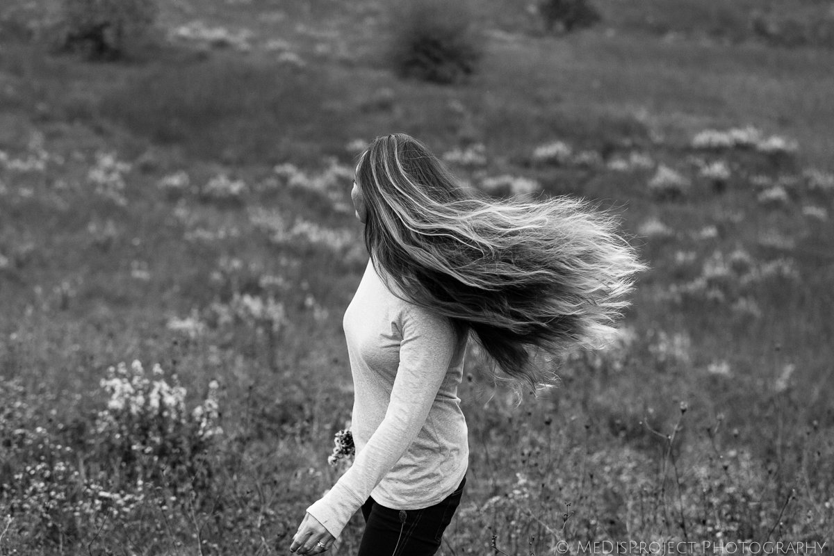 black and white photo of a lady's hair in the wind
