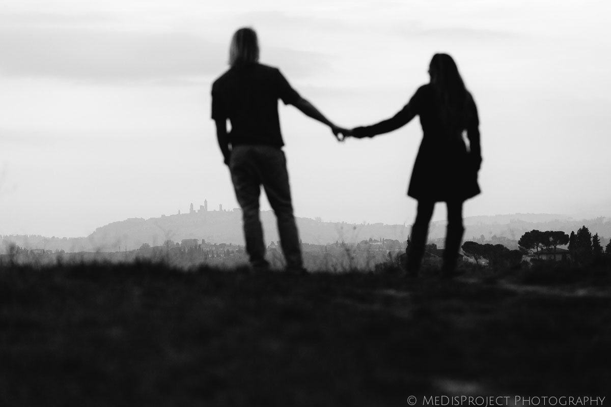 silhouette of a couple hand by hand staring at the gimignano skyline