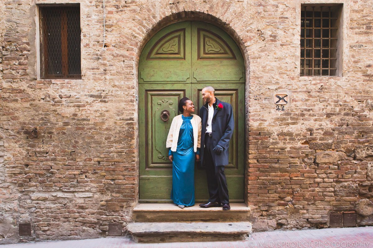 spouses posing at the old door