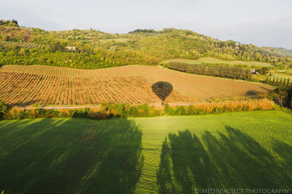 shadow of hot-air balloon over tuscan country