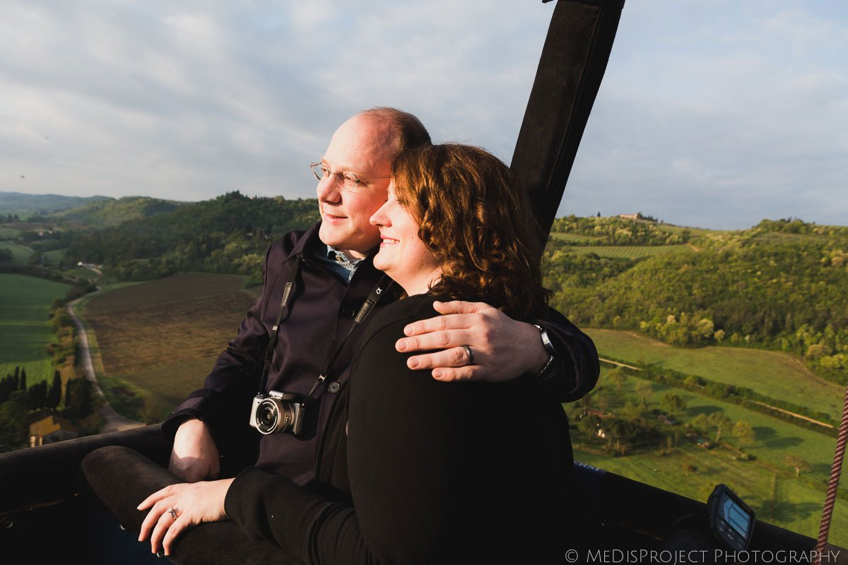 couple on a hot-air balloon over tuscan country