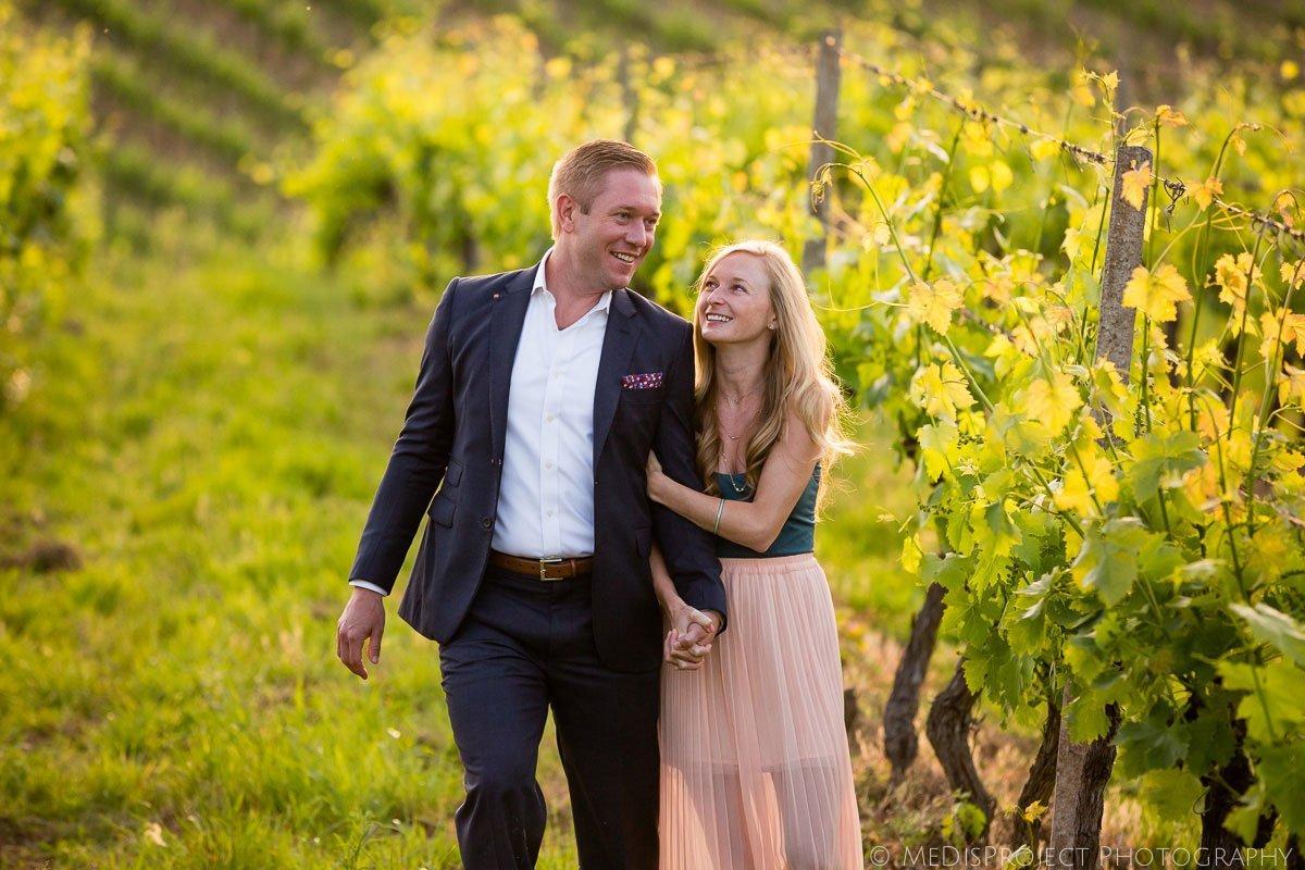 couple walking through a vineyard