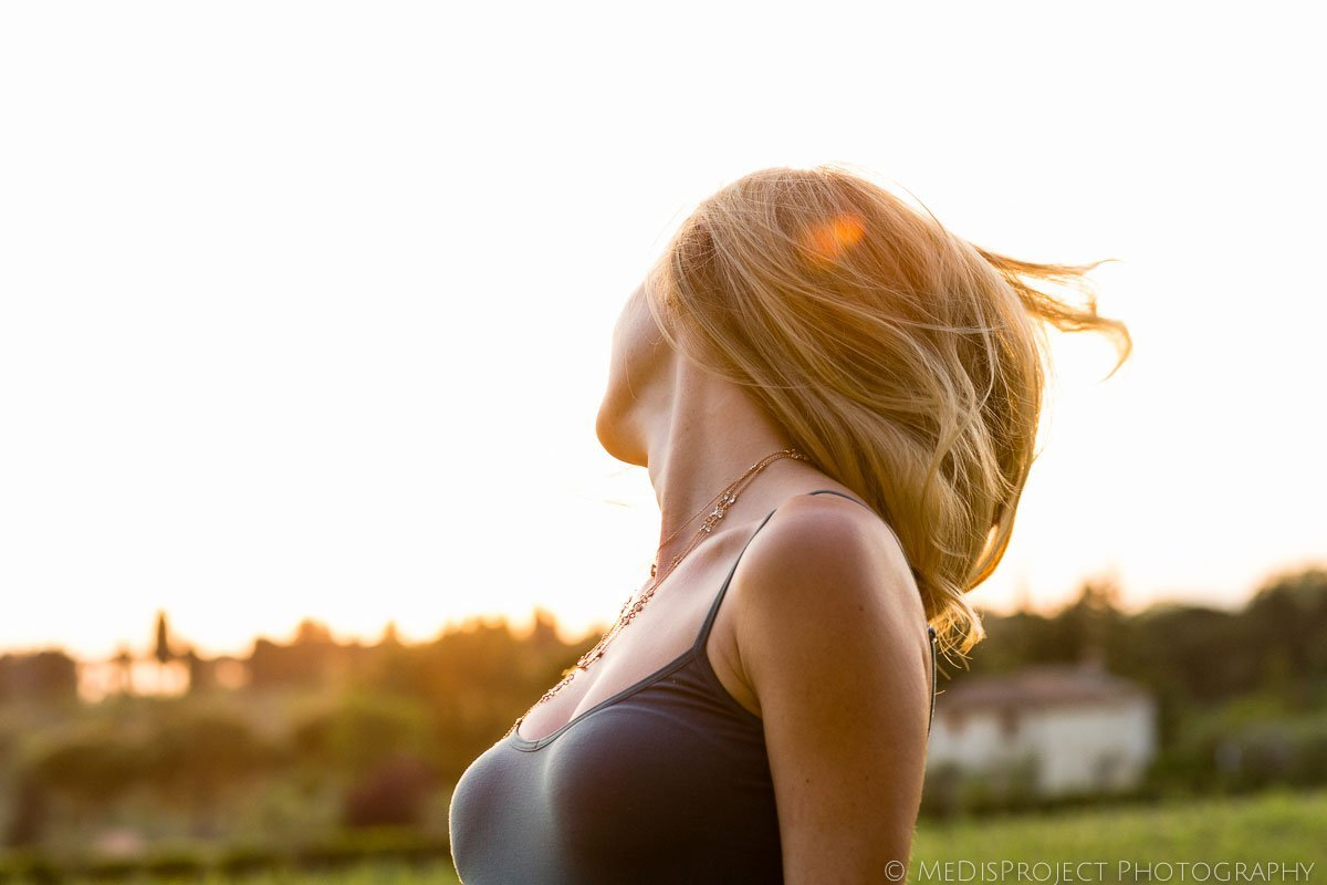blonde girl shaking her air in the sunset light