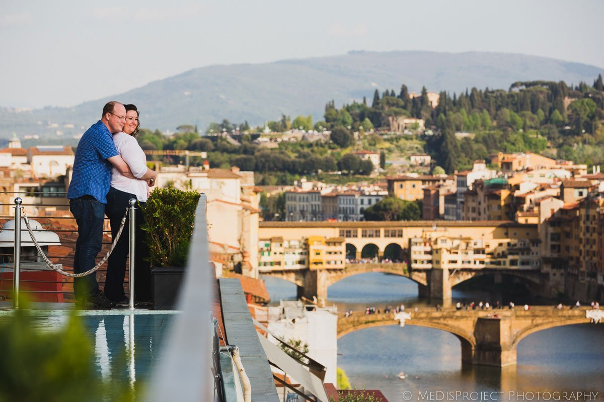 a couple embracing each other on arno river in florence