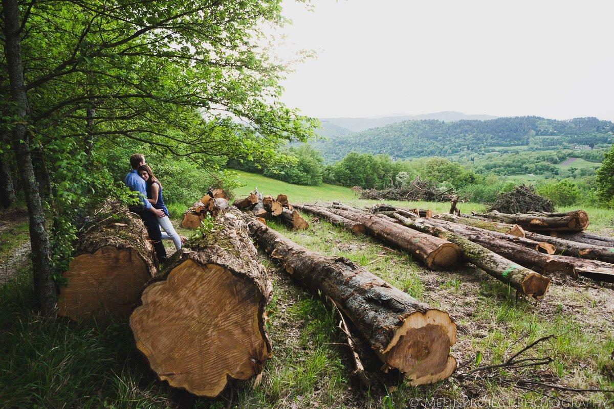 couple standing among tree trunks