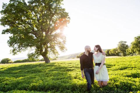 a couple walking in a field with a big oak as a backdrop