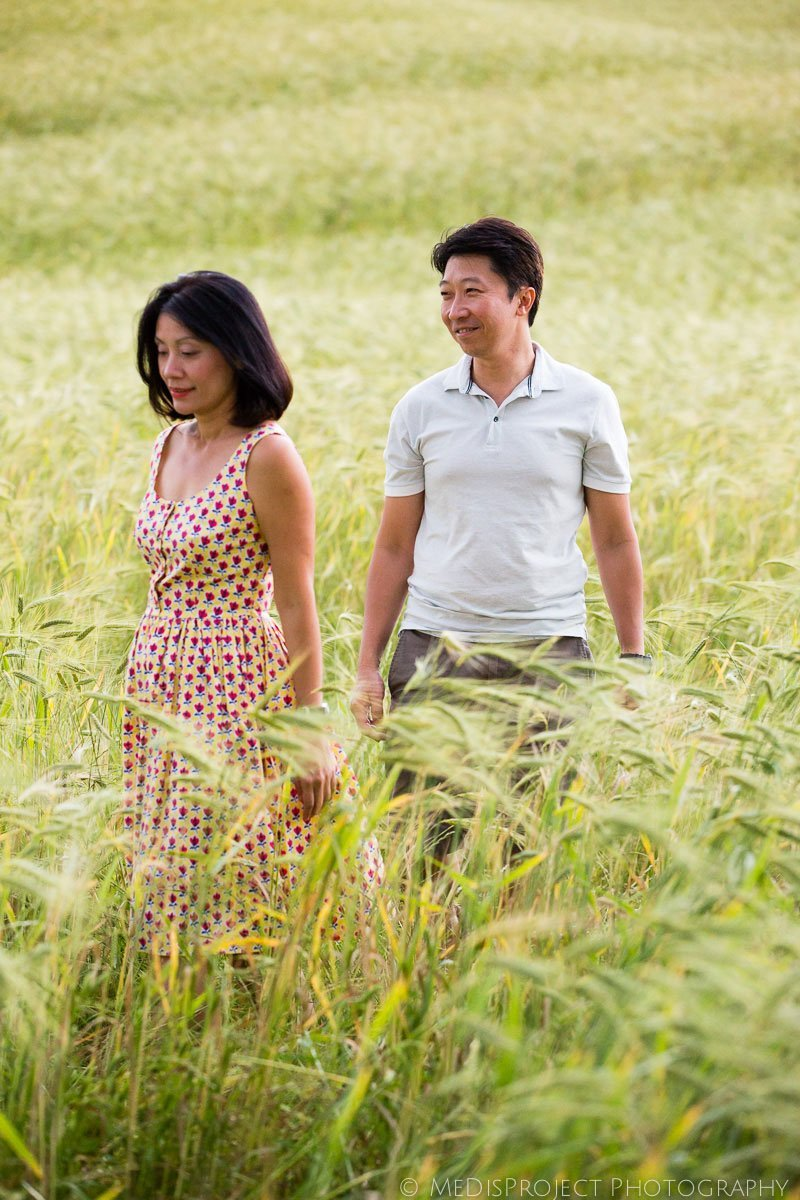 oriental couple walking in a wheat field