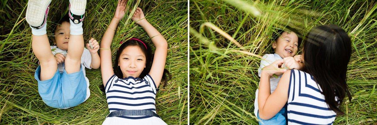 oriental kids laying in a wheat field