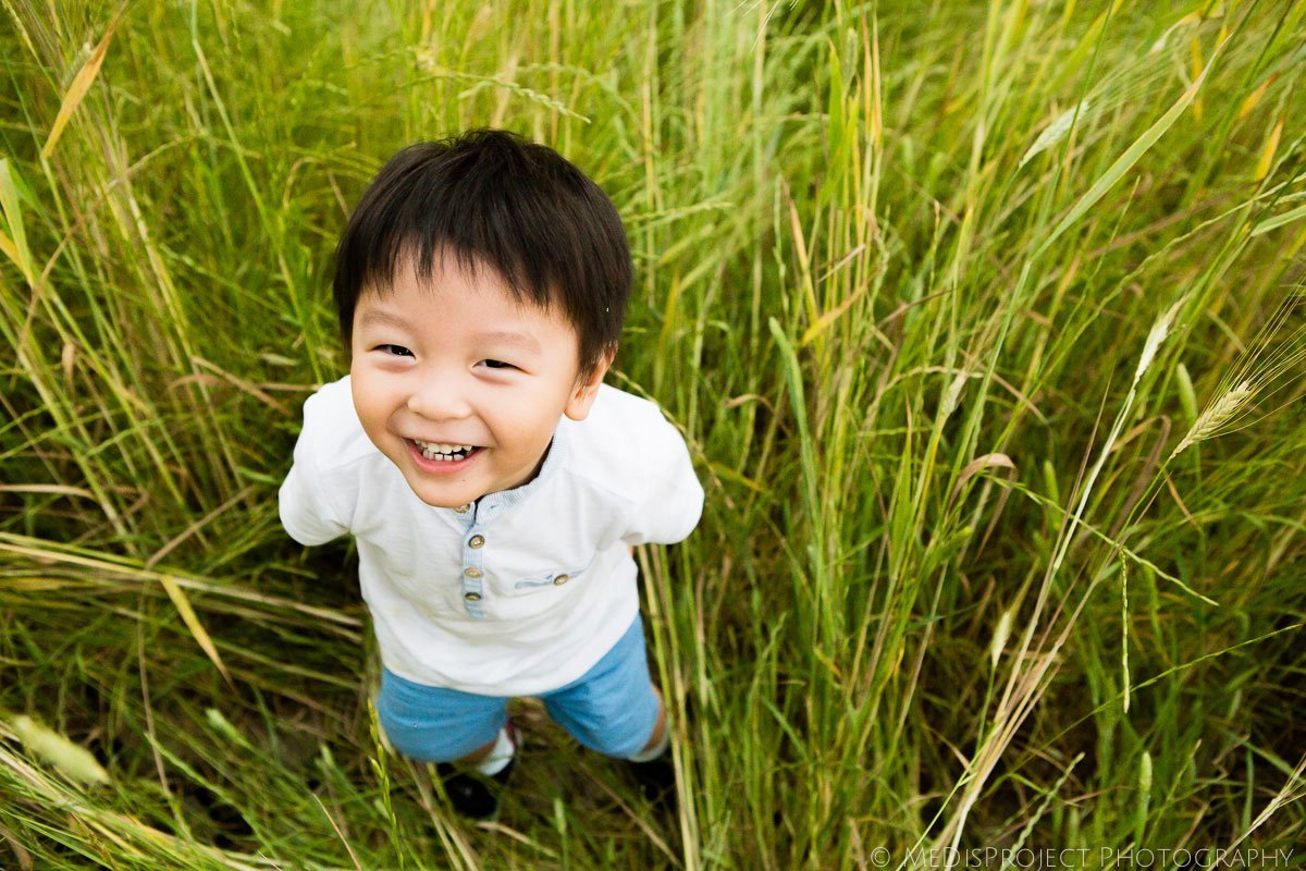 little oriental kid standing in a wheat field