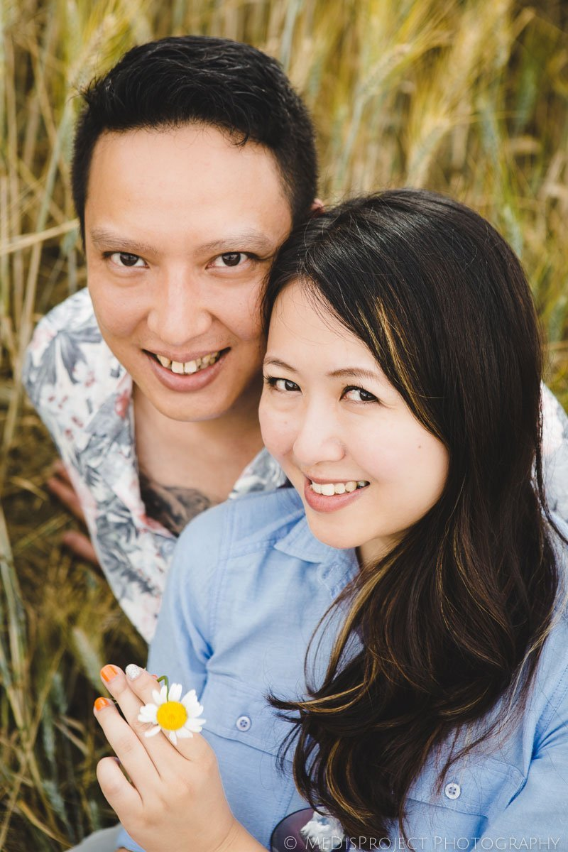 Chinese couple sitting in a grain field in Tuscany