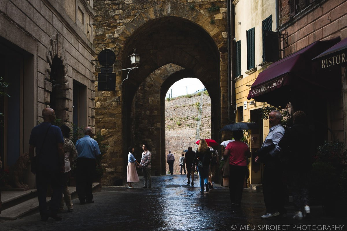chinese couple walking through the streets of Montepulciano during a summer rain