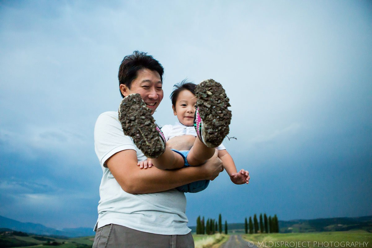 Oriental dad shows his son with muddy shoe soles