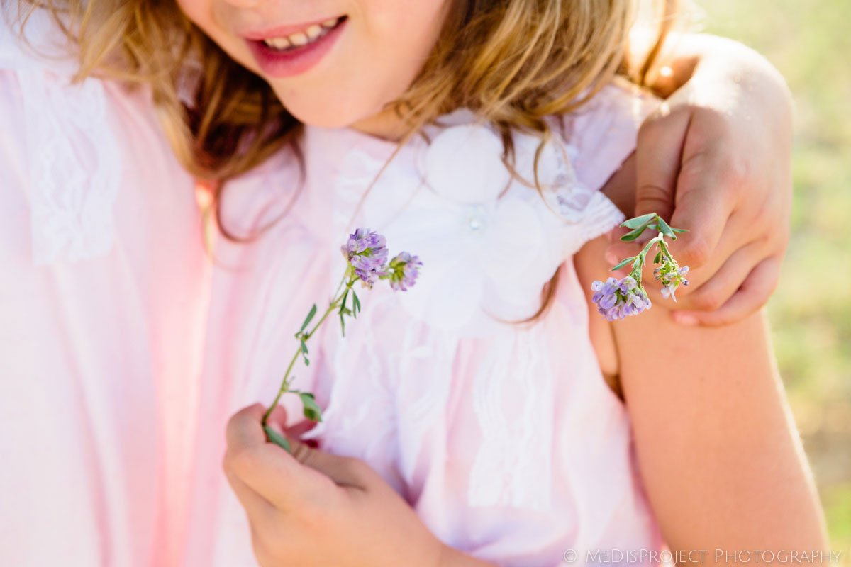 detail of a little girl dressed in pink holding a little wild flower