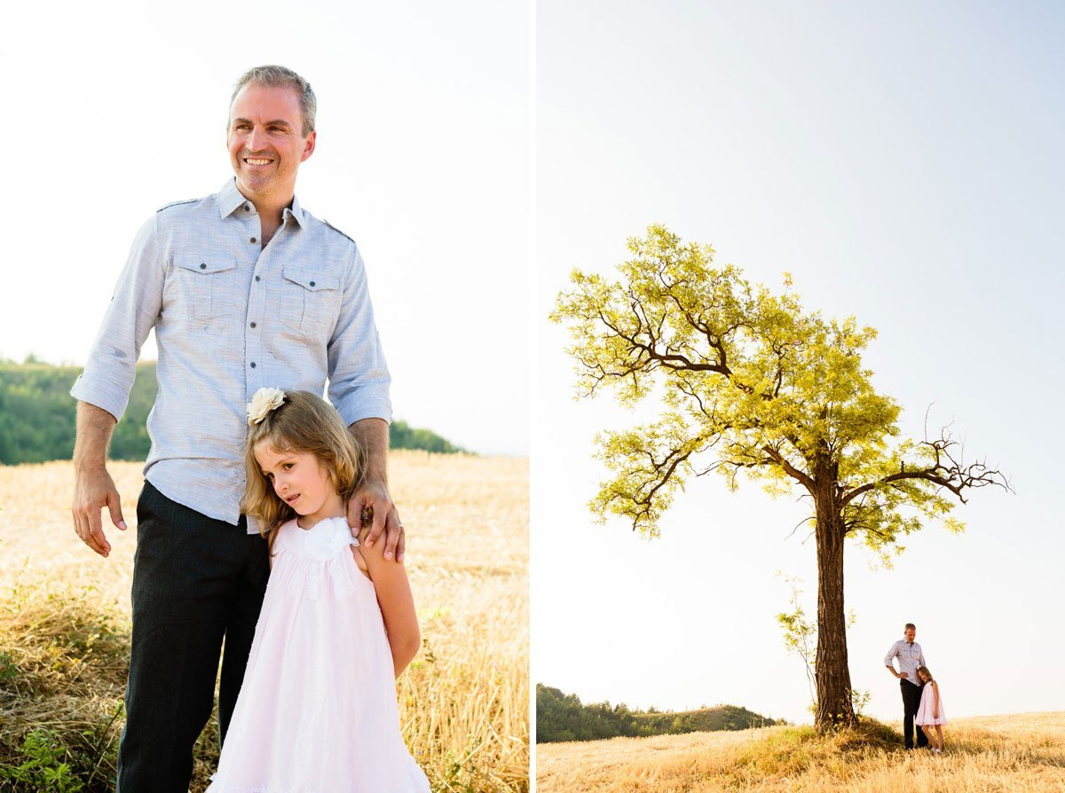father and daughter under a crooked tree on a stubble field