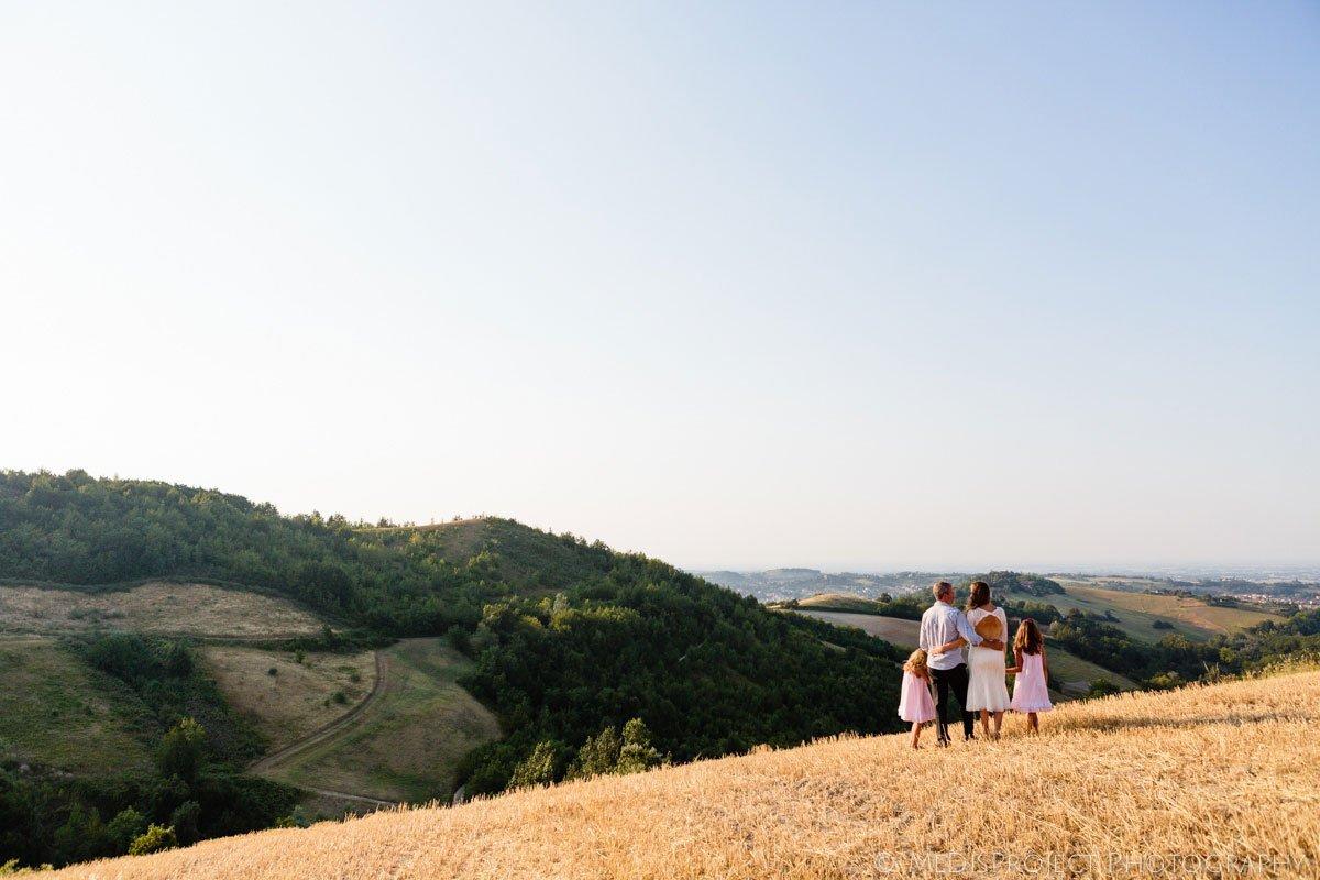 a family on a stubble field overlooking the Pianura Padana