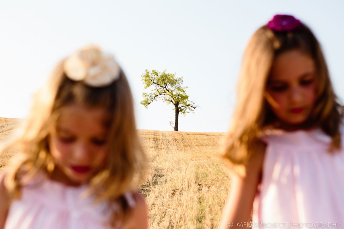 two little girls on a stubble field with a crooked tree on top