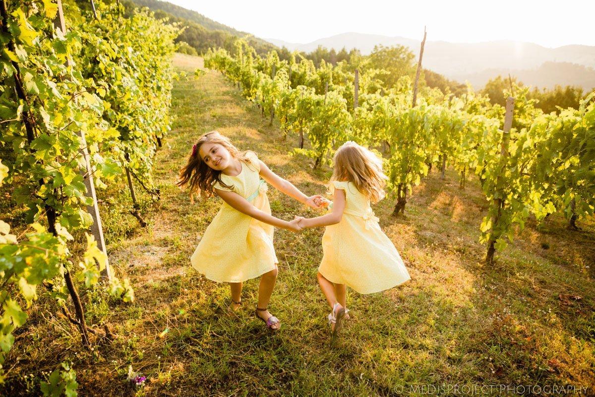 little girls dressed in yellow swinging in the vineyard