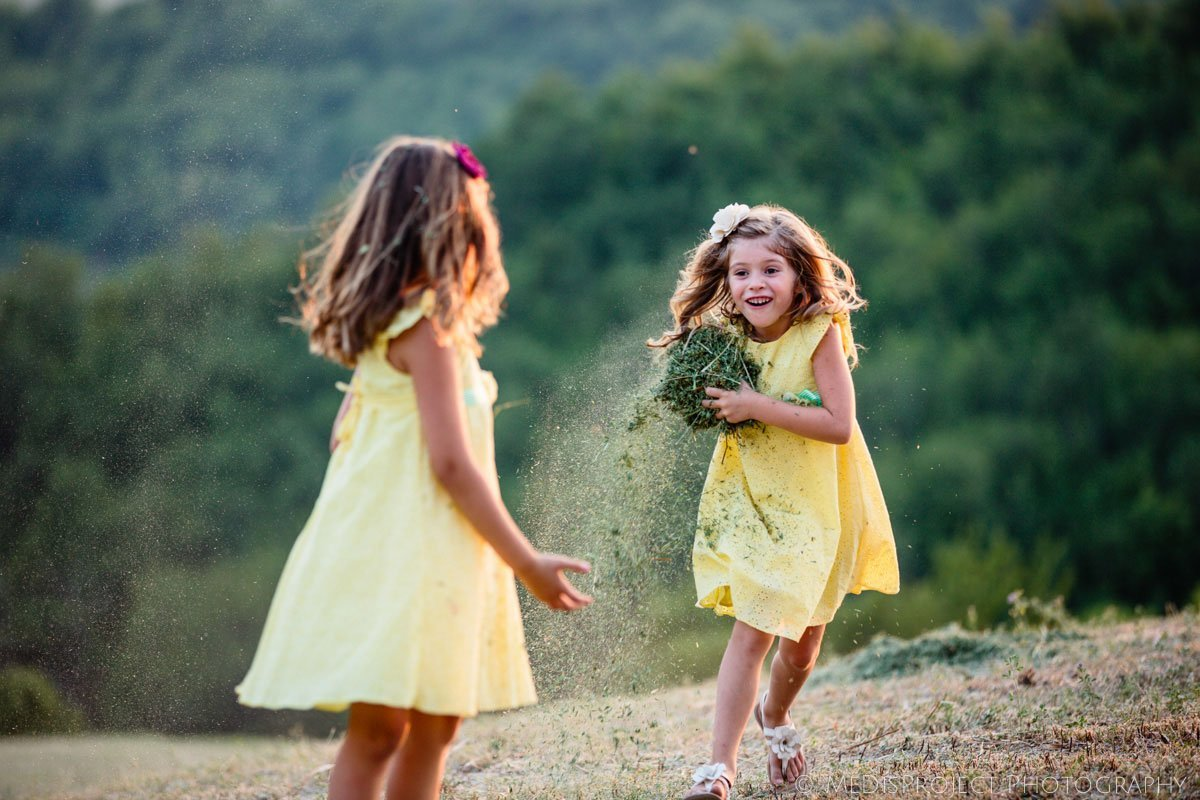 little girls dressed in yellow playing in the fields at sunset