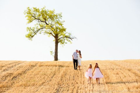 family portrait on a stubble field with a crooked tree on top