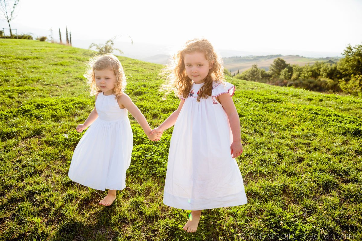 two little white angels playing on the grass