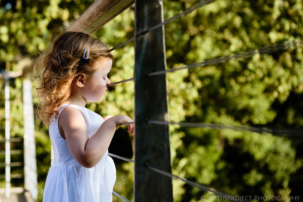 Little girls leaning with her nose to a fence