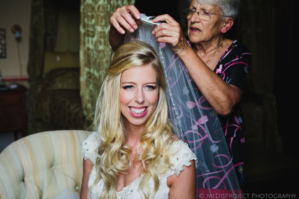 bride putting on the veil before wedding ceremony