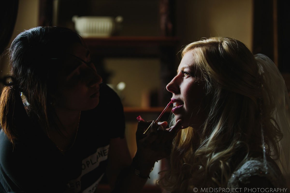 bride doing last makeup retouches before the wedding ceremony in Stomennano