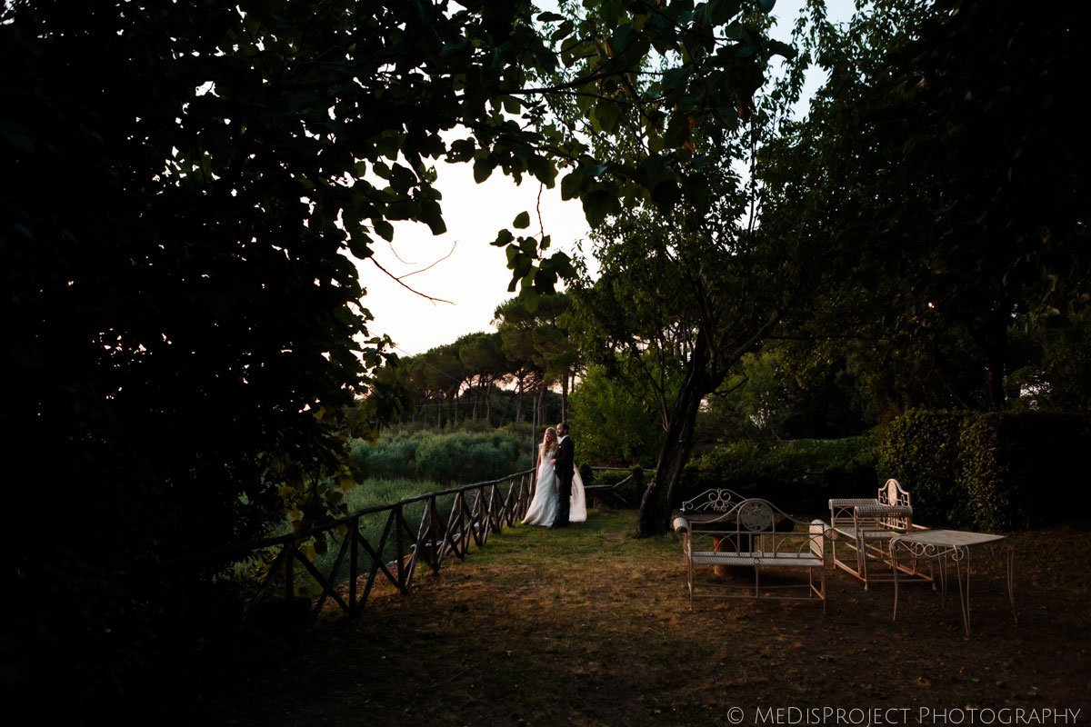 bride and groom hugging surrounded by trees in dusk golden light